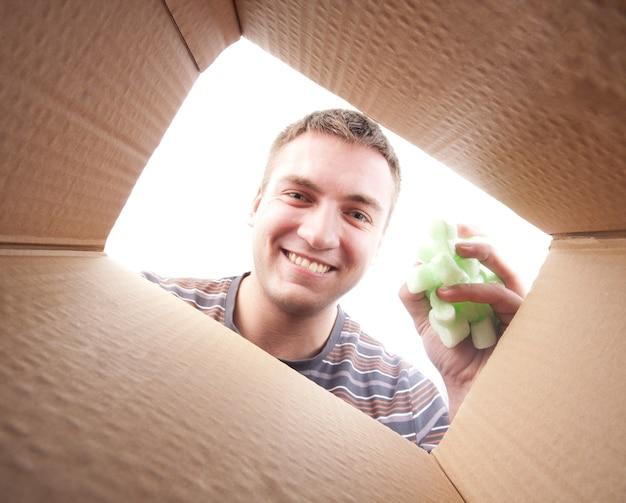 Man gooien polyfoam verpakking in kartonnen doos