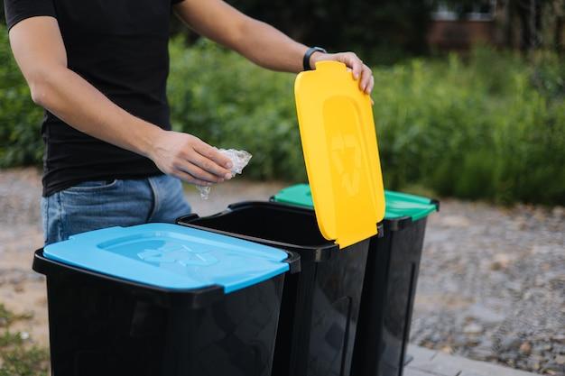 Man gooit plastic zak in prullenbak op achtertuin close-up van humen hand houd afval