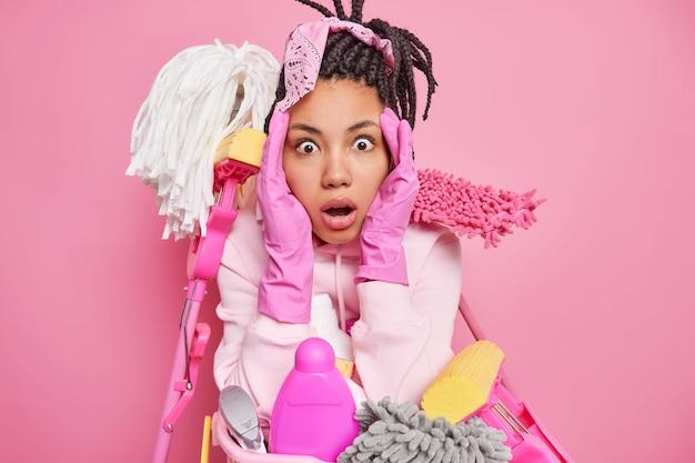 Man grijpt gezicht staart met omg uitdrukking kan niet geloven dat haar ogen veel werk aan huis heeft maakt gebruik van schoonmaakmiddelen weet niet hoe alles op orde te brengen