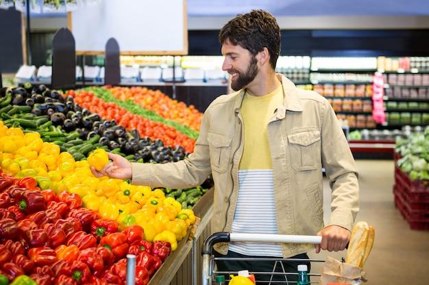 Man groenten in biologische winkel kopen
