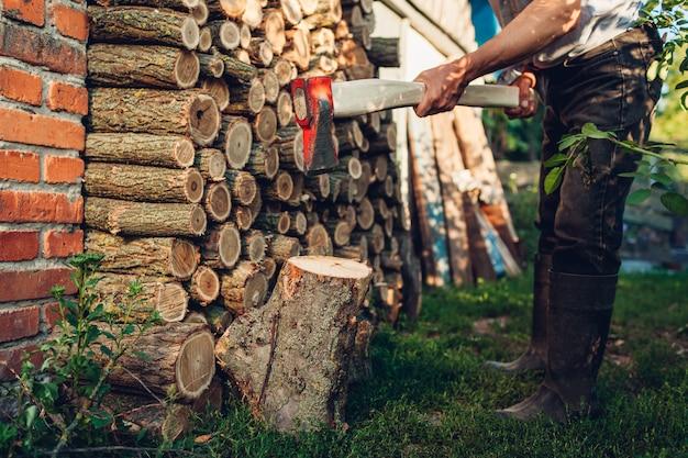 Man hakken brandhout met een bijl in platteland tuin