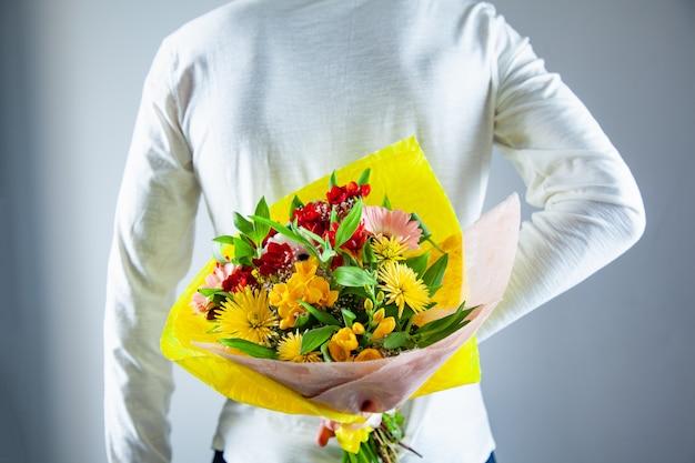 Man hand bloemen boeket in de rug