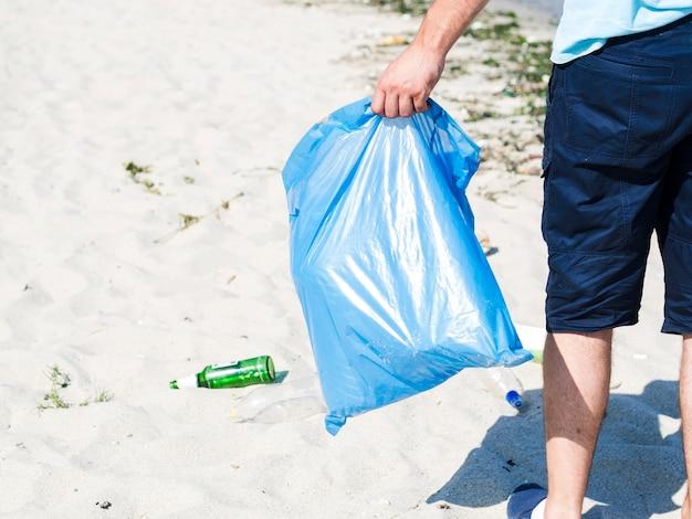 Man hand die blauwe vuilniszak op strand draagt