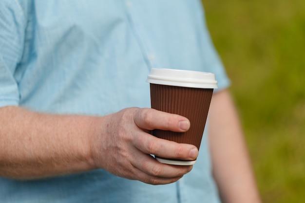 Man hand die document kop van koffie houdt. drink op straat