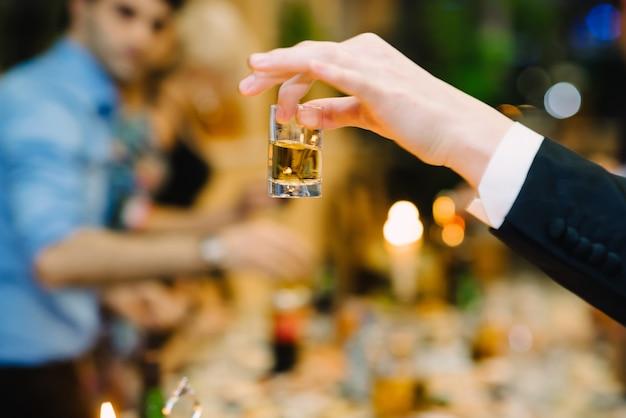 Man hand die een glas wodka in een restaurant op een vakantie houdt
