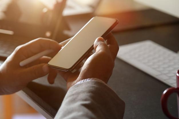 Man hand die en mobiele telefoon op werkruimte in bureau houden met behulp van