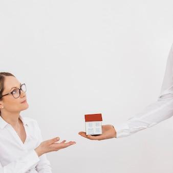 Man hand die miniatuurhuismodel geeft aan jonge vrouw tegen witte muur