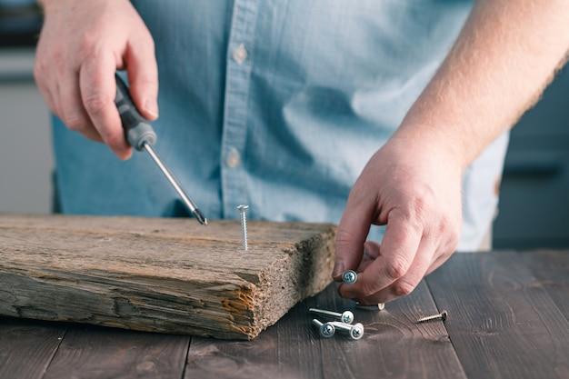 Man hand die schroevedraaier assembling wooden-plank gebruiken