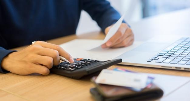 Man hand druk op rekenmachine en denken maandelijks over schuld facturen