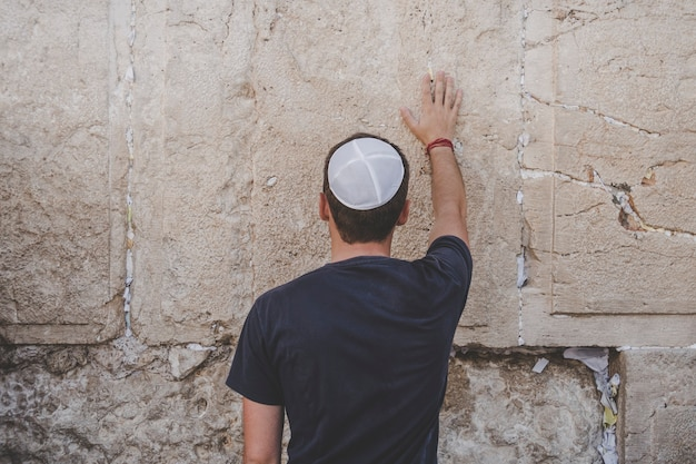Man hand en bid papier op de westelijke muur, klaagmuur, de plaats van huilen is een oude kalkstenen muur in de oude stad van jeruzalem. tweede joodse tempel door herodes de grote.