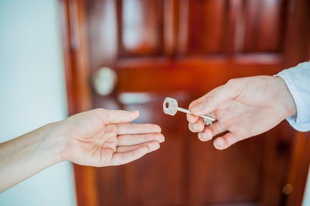 Man hand geeft een zeer belangrijk wijfje op achtergrond van houten deur. behandel het concept van onroerend goed