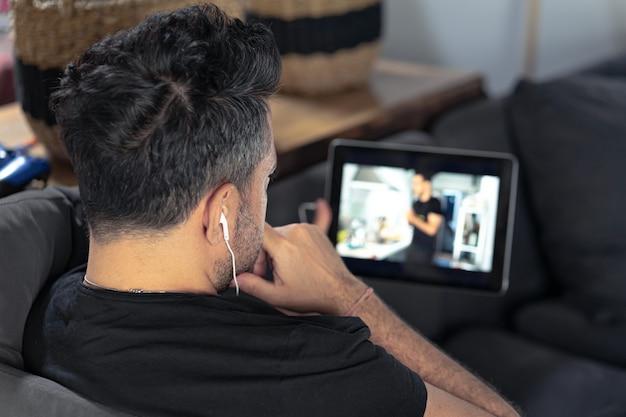 Man hand hebt met behulp van digitale tablet kijken naar online koken masterclass