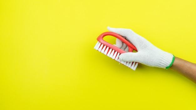 Man hand hebt met schoonmaakborstel op geel papier.