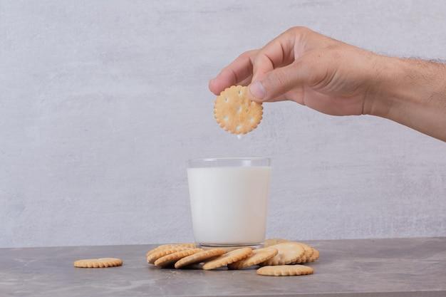 Man hand houdt een koekje bovenop melk op marmeren tafel.