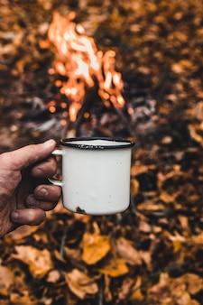 Man hand houdt een warme kop koffie op de achtergrond van het kampvuur.