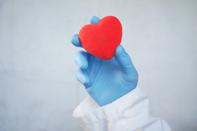 Man hand in beschermende handschoenen met rood hart op witte achtergrond