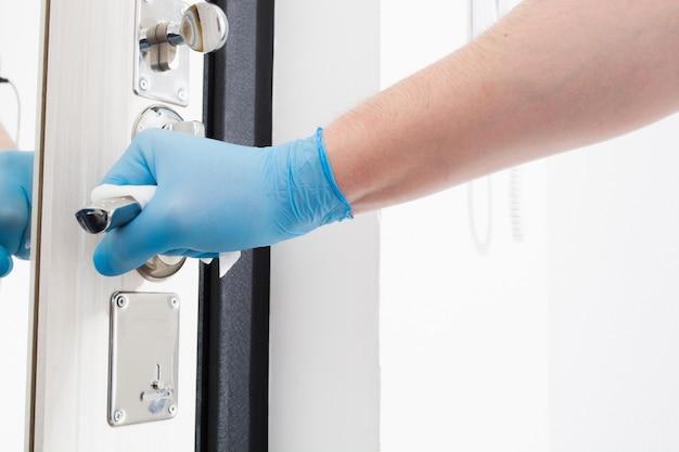 Man hand in blauwe handschoen schoonmaken deurknop met wegwerp servet quarantainetijd