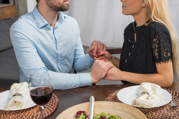 Man hand in hand met blonde vrouw aan tafel