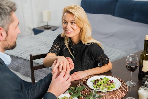 Man hand in hand van de vrouw aan tafel