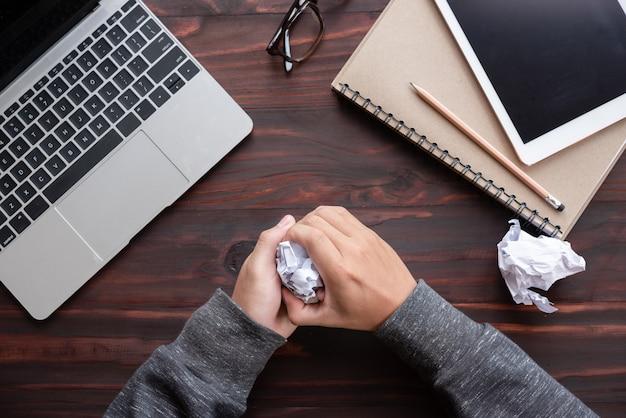Man hand is verfrommeld papier aan mannen tafel op kantoor proberen te komen met de juiste oplossing