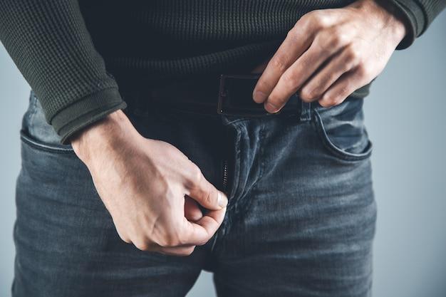 Man hand ketting in broek op grijze achtergrond