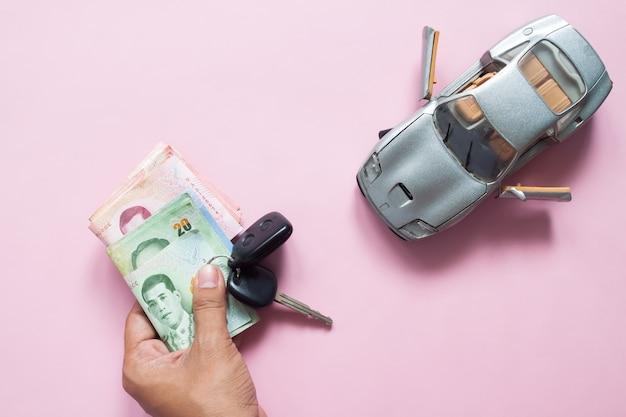 Man hand met auto sleutel en thaise bankbiljetten met automodel op roze achtergrond