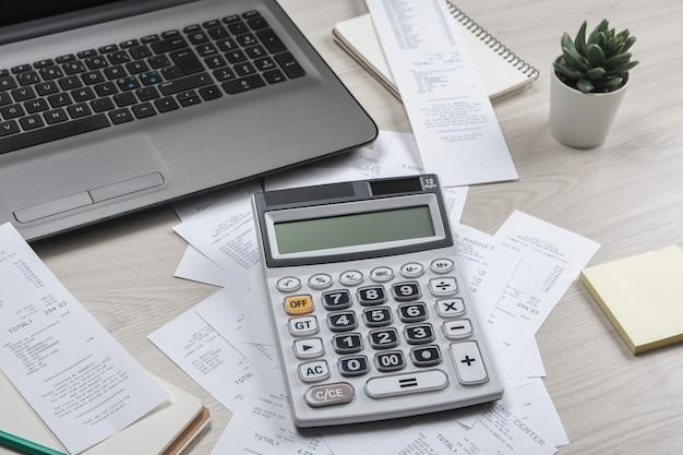 Man hand met behulp van rekenmachine en schrijven notitie maken met berekenen over kosten en belastingen op kantoor aan huis. zakenman doet wat papierwerk op de werkplek