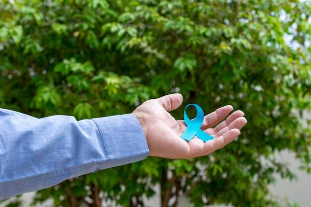 Man hand met blauw lint. blauwe november. prostaatkanker preventie maand. de gezondheid van mannen.