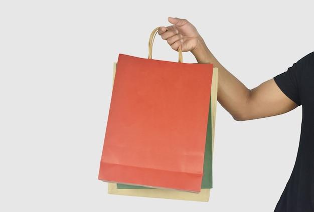 Man hand met boodschappentassen op grijze achtergrond met uitknippad