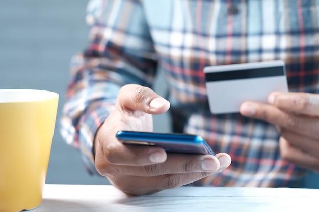 Man hand met creditcard en met behulp van slimme telefoon online winkelen.
