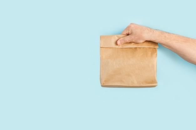 Man hand met een bruine papieren zak op een lichtblauwe achtergrond