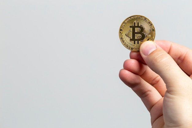 Man hand met een fysieke bitcoin voor een witte achtergrond
