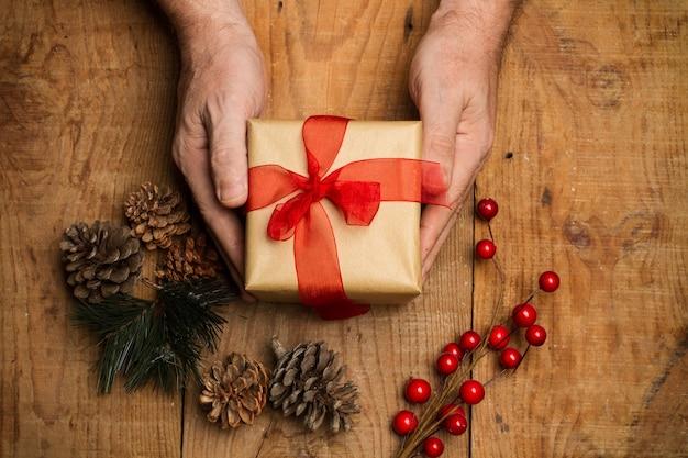Man hand met een kerstpakket op een rustieke houten tafel