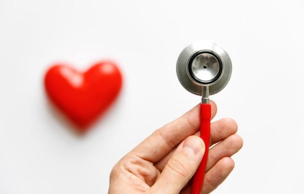 Man hand met een rode stethoscoop - medisch diagnostisch apparaat voor auscultatie (luisteren) van geluiden die uit het hart, bronchiën, geïsoleerd komen