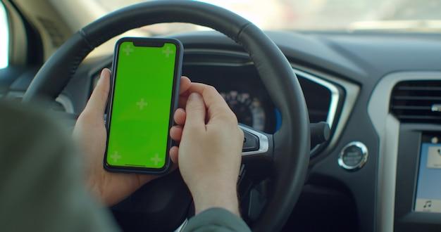 Man hand met een smartphone met groen leeg scherm in de elektrische auto voor richting