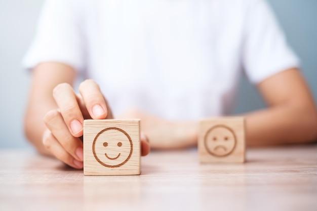 Man hand met emotie gezicht blok. klant kiest emoticon voor gebruikersrecensies. servicebeoordeling, rangschikking, klantbeoordeling, tevredenheid, evaluatie en feedbackconcept