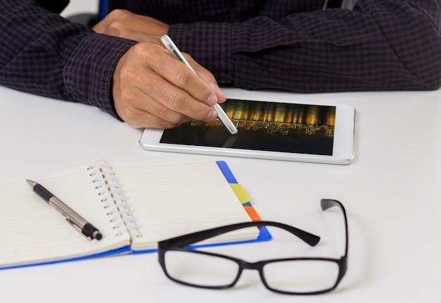 Man hand met stylus pen op moderne digitale tablet pc op de werkplek