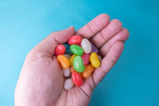 Man hand met verschillende jelly beans op de blauwe achtergrond blue