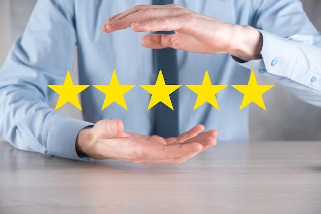 Man hand met vijf sterren uitstekende rating.