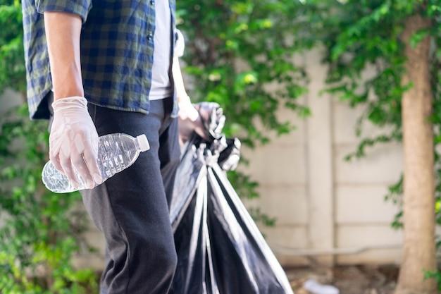 Man hand met vuilniszak om te gaan gooien in de prullenbak in buitenpark