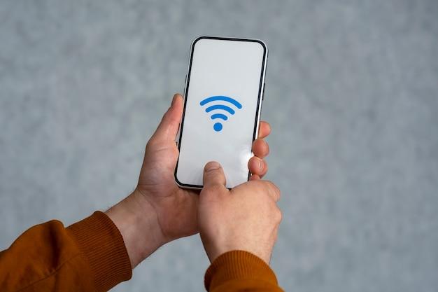 Man hand met zilveren smartphone geïsoleerd op een lichte achtergrond. telefoonmodel met wit scherm en wifi-pictogram.