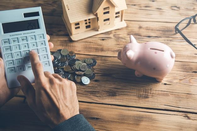 Man hand munten met rekenmachine en huismodel op bureau