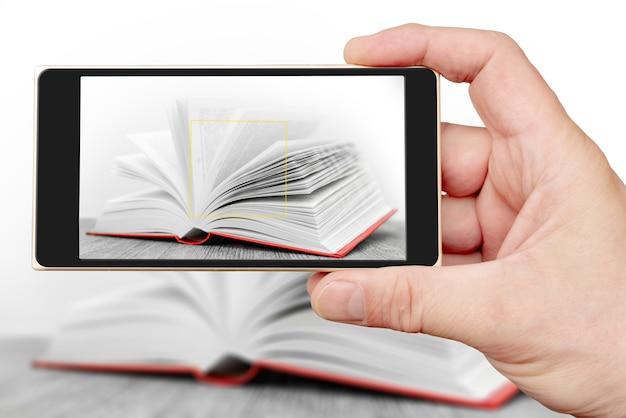 Man hand neemt een foto met smartphone om boek te openen.