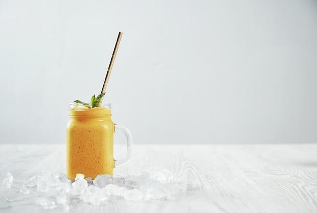 Man hand neemt transparante rustieke pot met smakelijke, gezonde, vers gemaakte gele smoothie van mango