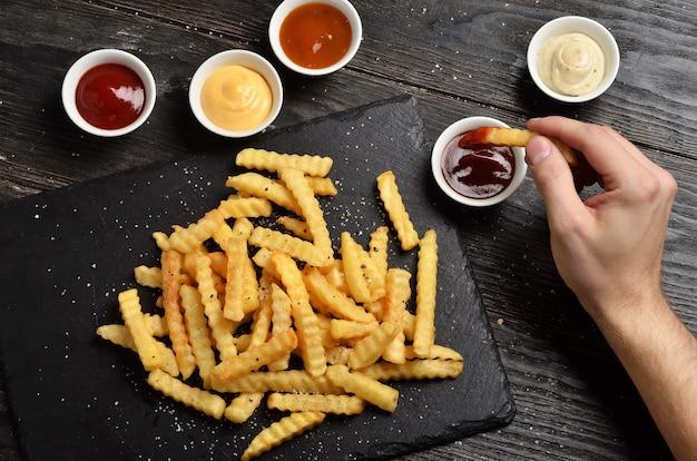 Man hand onderdompelende frieten in barbecuesaus