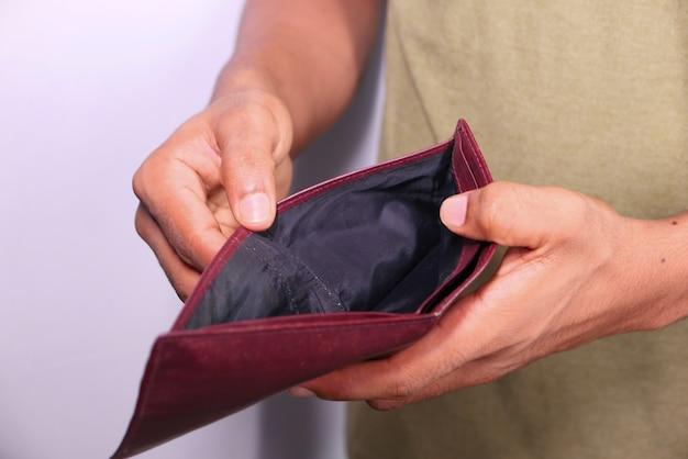 Man hand opent een lege portemonnee met kopie ruimte.