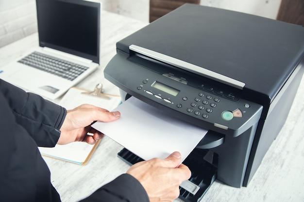 Man hand papier in printer en computer op tafel