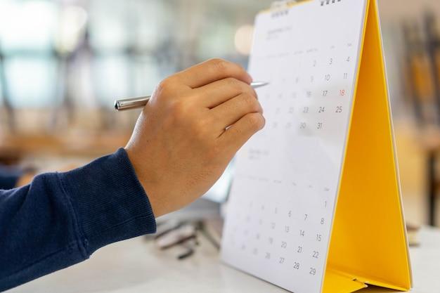 Man hand pen naar aanwijsschema (tijdschema) of markeer belangrijke dag op kalender