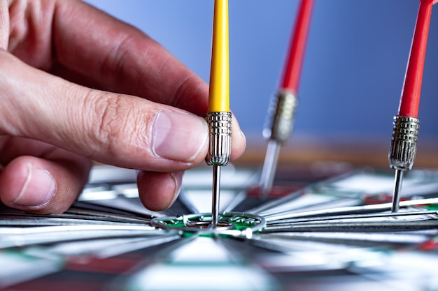 Man hand pijl op midden van dartbord