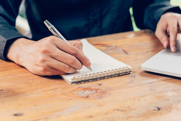 Man hand schrijven notitieboekje papier en met behulp van telefoon op houten tafel in de koffiewinkel met vintage toned filter.